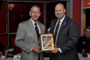 Jim Taliaferro presents 1st Annual Trey Hutchison Civilian of the Year Award to the son of the late Caddo Parish District Attorney Charles Rex Scott.